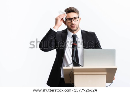 scared businessman in suit standing at podium tribune and holding napkin during conference isolated on white  Foto stock ©