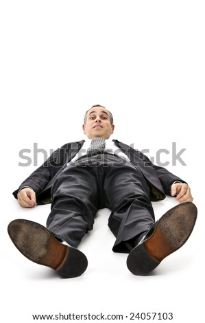 Scared businessman laying down in a suit isolated on white background
