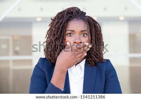 Scared businesswoman shocked with news. Young African American business woman with wide eyes standing outside, covering mouth with hand. Shock concept