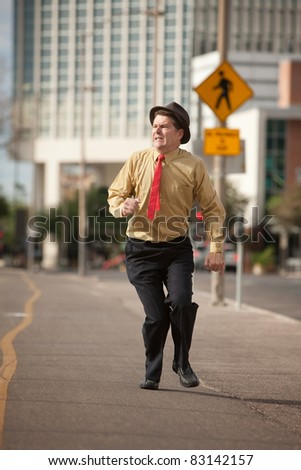 Scared Caucasian businessman run down the street