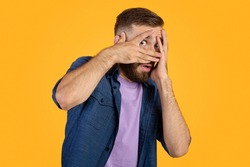 Scared Caucasian guy hiding behind his hands, peeping between fingers on orange studio background. Horrified young man suffering from phobia, feeling spooked. Negative emotions concept