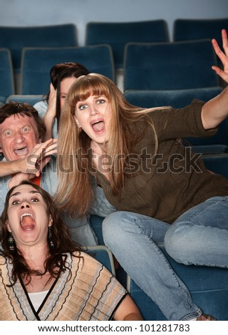 Scared Caucasian teen jumps out of her seat in theater