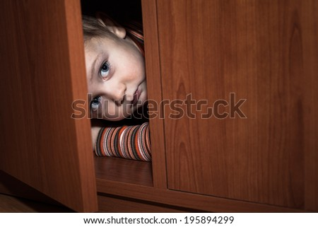 scared child boy hiding in...