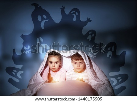 Scared children in pajamas with flashlights hiding under blanket. Frightened kids sitting in bed. Children and boo ghosts above them. Comic evil spirits silhouettes on background. Childhood fears. #1440175505