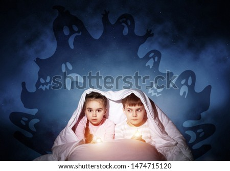 Scared children in pajamas with flashlights hiding under blanket. Frightened kids sitting in bed. Children and boo ghosts above them. Comic evil spirits silhouettes on background. Childhood fears. #1474715120