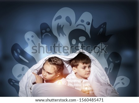 Scared children in pajamas with flashlights hiding under blanket. Frightened kids sitting in bed. Children and boo ghosts above them. Comic evil spirits silhouettes on background. Childhood fears. #1560485471