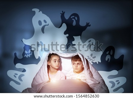 Scared children in pajamas with flashlights hiding under blanket. Frightened kids sitting in bed. Children and boo ghosts above them. Comic evil spirits silhouettes on background. Childhood fears. #1564852630