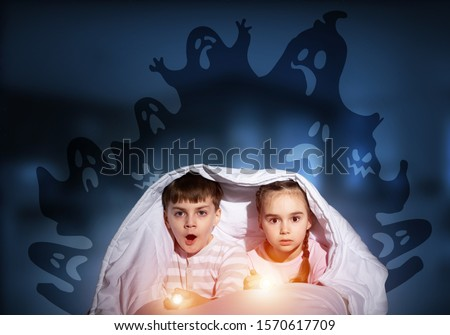 Scared children in pajamas with flashlights hiding under blanket. Frightened kids sitting in bed. Children and boo ghosts above them. Comic evil spirits silhouettes on background. Childhood fears. #1570617709