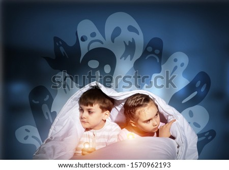 Scared children in pajamas with flashlights hiding under blanket. Frightened kids sitting in bed. Children and boo ghosts above them. Comic evil spirits silhouettes on background. Childhood fears. #1570962193