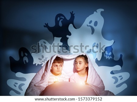 Scared children in pajamas with flashlights hiding under blanket. Frightened kids sitting in bed. Children and boo ghosts above them. Comic evil spirits silhouettes on background. Childhood fears. #1573379152