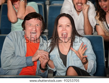 Scared couple and group of people scream in a theater