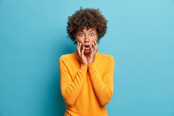 Scared dark skinned young woman stares bugged eyes and holds face keeps mouth opened wears casual jumper poses indoor. Frightened Afro American girl gazes scaredly at something embarrassing.
