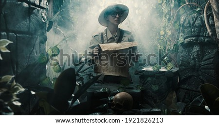 Scared explorer lost in the jungle: she is holding a map and looking at some ancient ruins Photo stock ©