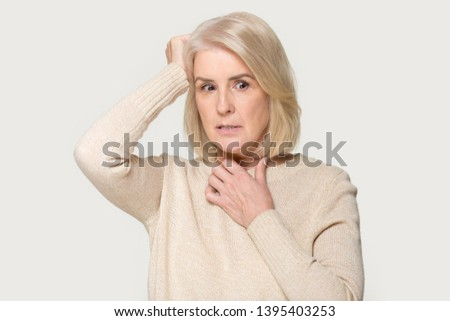 Scared face expressions of old woman touch head feels frightened isolated on grey studio background, concept of memory loss dementia or brain damage, decreased mind activity, age psychological changes