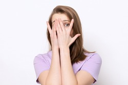 scared girl hiding face in palms hands and peering out with one eye between her fingers, trembling fear, very terrified over scary creepy sound, isolated over white background