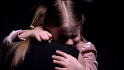 Scared girl hiding in mothers embrace, victims of domestic violence, close-up