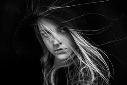 scared girl in black hood looking back in dark monochrome