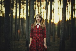 scared girl in the woods. girl in a red dress scared of deforestation