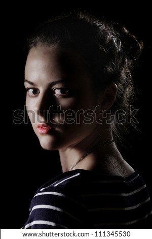 scared girl looking back on dark background