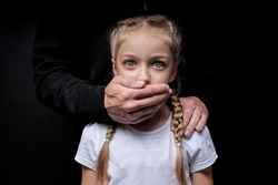 Scared girl with closed mouth by maniac killer, looking at camera with wide opened eyes, male hands on kid's shoulders, kidnapping, pedophile with child girl