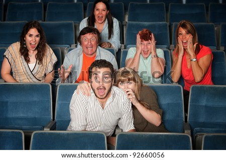 Scared group of people scream out in theater