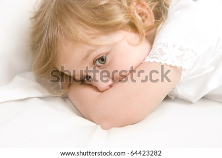 Scared little blond girl in the bed close-up