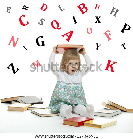 Scared little child sitting on the floor surrounded by books and alphabetical letters