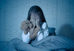 Scared little girl sitting in bed covering her face with hands holding her teddy in fear afraid of monsters in darkness in bedroom in Child nightmares imagination and psychological distress concept.