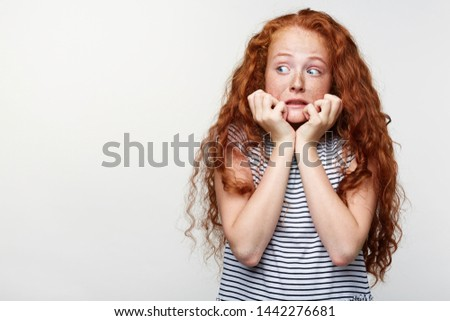 Scared little girl with ginger hair and freckles, afraid and anxious biting her finger nails, looking at camera with wide opened eyes and looks away, isolated over white background with copy space.