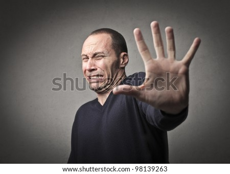 Scared man indicating to halt with his hand