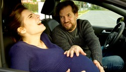 Scared man shouting with wife giving birth in car