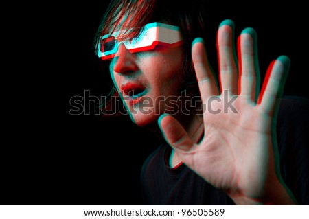 Scared man with anaglyph glasses watching a 3D movie, anaglyph image.
