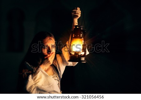 Scared Medieval Princess Holding Lantern - Portrait of terrified woman wearing a vintage dress holding a lamp