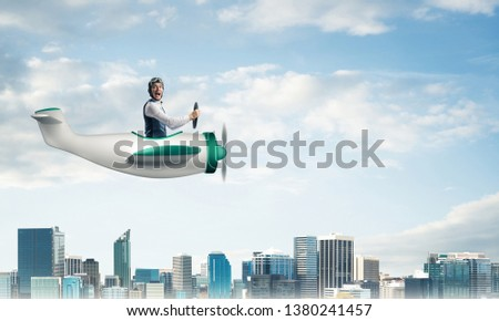 Scared pilot with open mouth sitting in cabin of small airplane. Funny man in aviator hat and goggles driving propeller plane above city. Modern metropolis with high buildings and towers. #1380241457