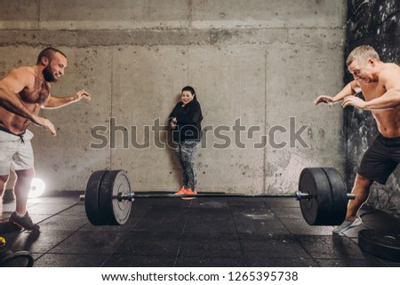 scared plump woman is afraid of falling huge barbell. fear, phobia.dangerous, extreme, traumatic sport. emergency situation. shock.