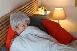 Scared senior woman hiding under blankets