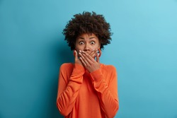 Scared shocked African American woman covers mouth, stares with eyes full of fear, dressed in casual orange jumper, cannot believe in awful news, isolated on blue background. Frightened female model