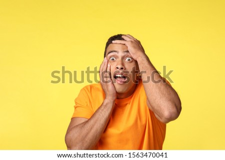 Scared, stunned and speechless frightened handsome man, grab head gasping, open mouth and stare away terrified, feeling fear and discomfort, trembling from horror, stand yellow background