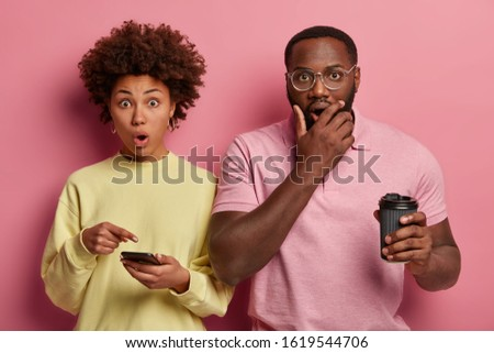 Scared stupefied woman points at display of smartphone, shock receive message, her dark skinned husband covers mouth and gasps from surprisement, drinks takeway coffee, react on stunning situation