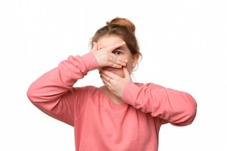 scared teen girl hiding face in palms hands and peering out with one eye between her fingers, trembling fear, very terrified over scary creepy sound, isolated over white background