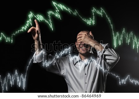 Scared trader pointing to stock market charts with eyes closed. Uncertainty concept photo.