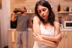 Scared woman after she gets a beating from drunk and acoholic husband. Violent aggressive man abusing injuring terrified helpless, vulnerable, afraid, beaten and panicked wife, victim.