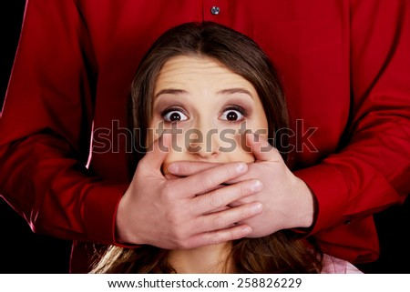 Scared woman has mouth covered by a man.