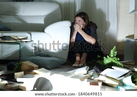 Scared woman hiding from intruder during home robbery sitting on the floor in the night