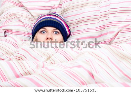 Scared woman in winter hat hiding wrapped in duvet.