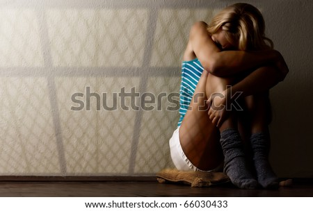 Scared woman sitting on floor with windows grid shadows.