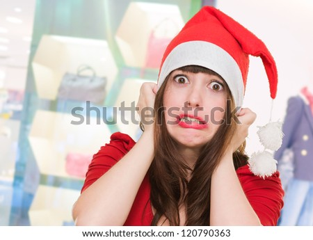 scared woman wearing a christmas hat in front of a shop