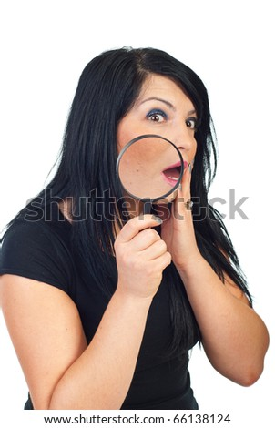 Scared woman with acne holding a magnifying glass and checking her face in the mirror isolated on white background