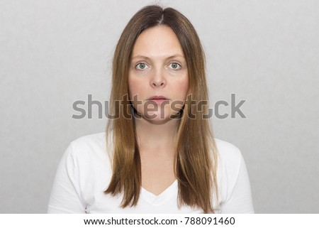 Scared woman without make-up looks at the camera on a gray background portrait, beauty.