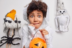 Scared worried curly haired African American woman holds carved pumpkin afraids of spooky creatures around bites lips dresses up in ghost cotume isolated over white background. Halloween concept